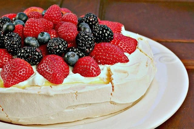 Pavlova with lemon curd on a white plate garnished with fresh berries