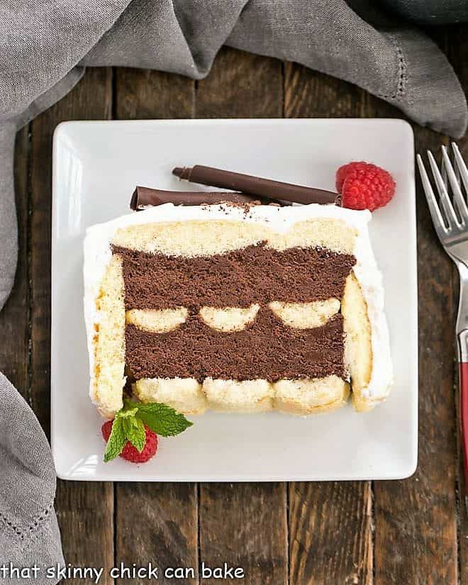 Slice of chocolate mousse cake with ladyfingers on a square white dessert plate