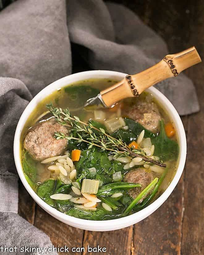 Overhead view of a bowl of Italian Wedding soup with a bamboo handled spoon holding a meatball