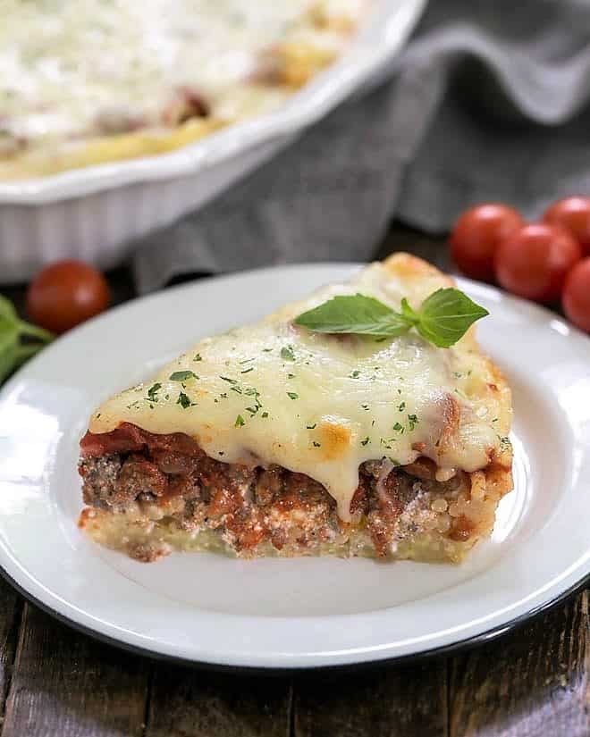 Slice of spaghetti pie topped with a sprig of basil on a white plate