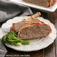 Bacon wrapped meatloaf slices on a white dinner plate with a fork and two broccoli spears