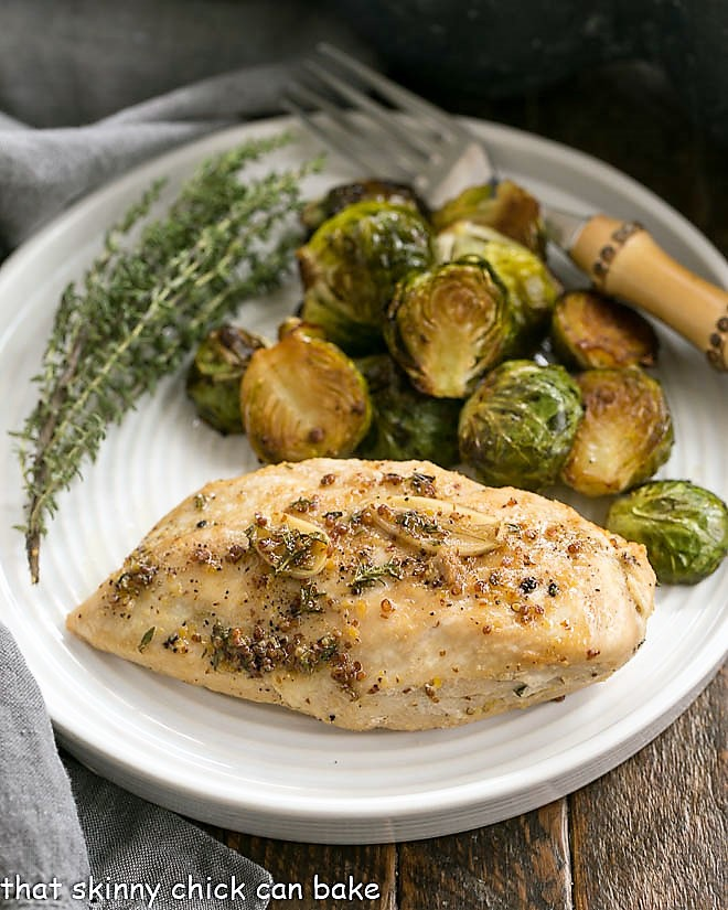 Maple-Glazed Chicken on a dinner plate with Brussels sprouts and a thyme garnish