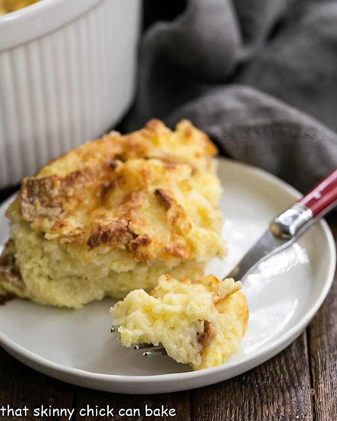 Bite of cheese souffle on a red handled fork on a plate