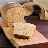 Sliced loaf of Honey Oatmeal Bread on a wooden cutting board