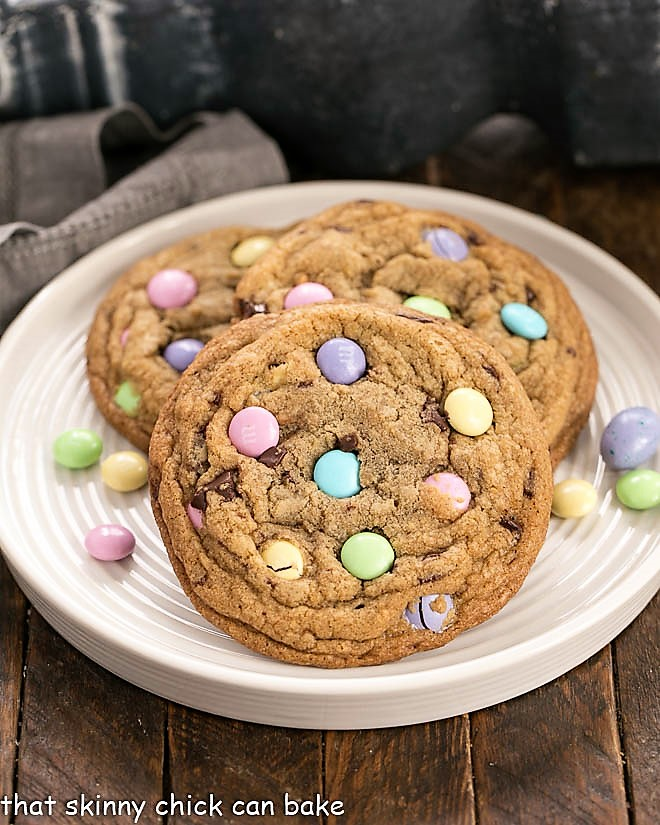 3 Brown Butter Easter Cookies on a rimmed white place surrounded by pastel M&M's