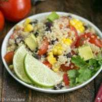 Quinoa Salad in a white bowl with a lime garnish