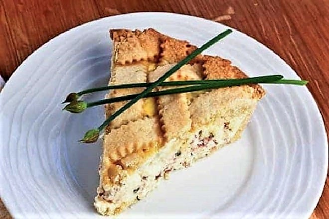 Pizza rustica on a white plate topped with blossoming chives
