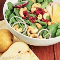 A bowl of spinach salad with pears, craisins and cashews