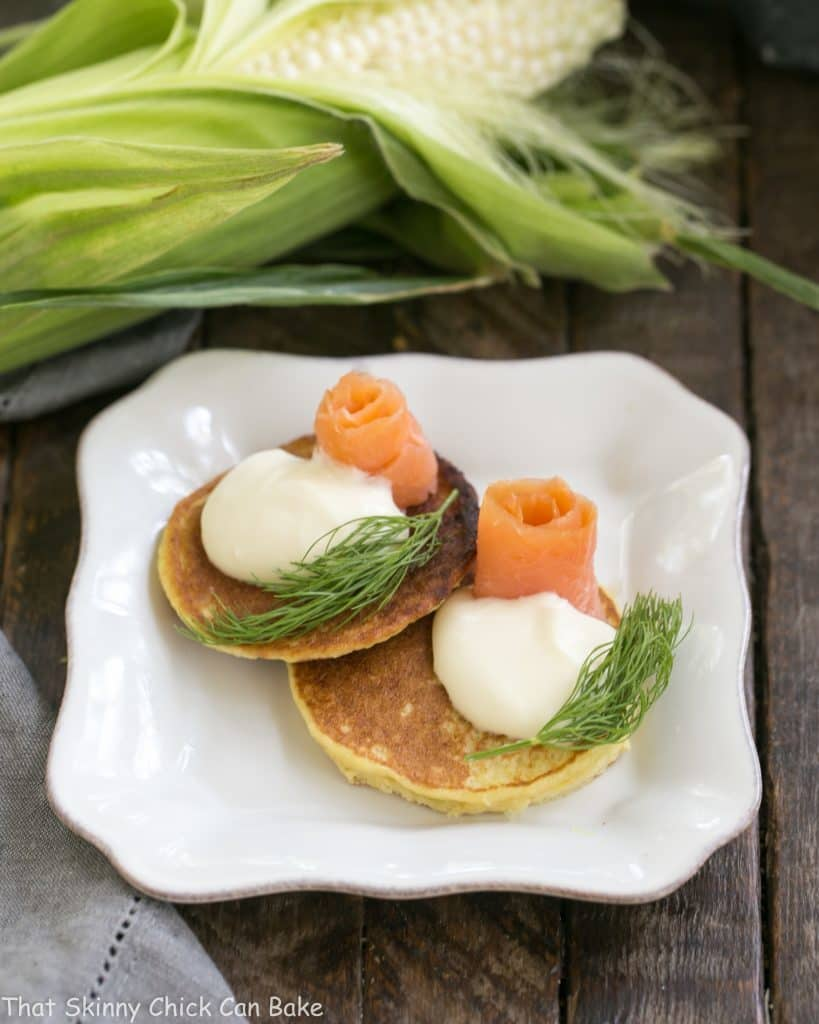 Fresh Corn Pancakes on a square plate topped with salmon and dill