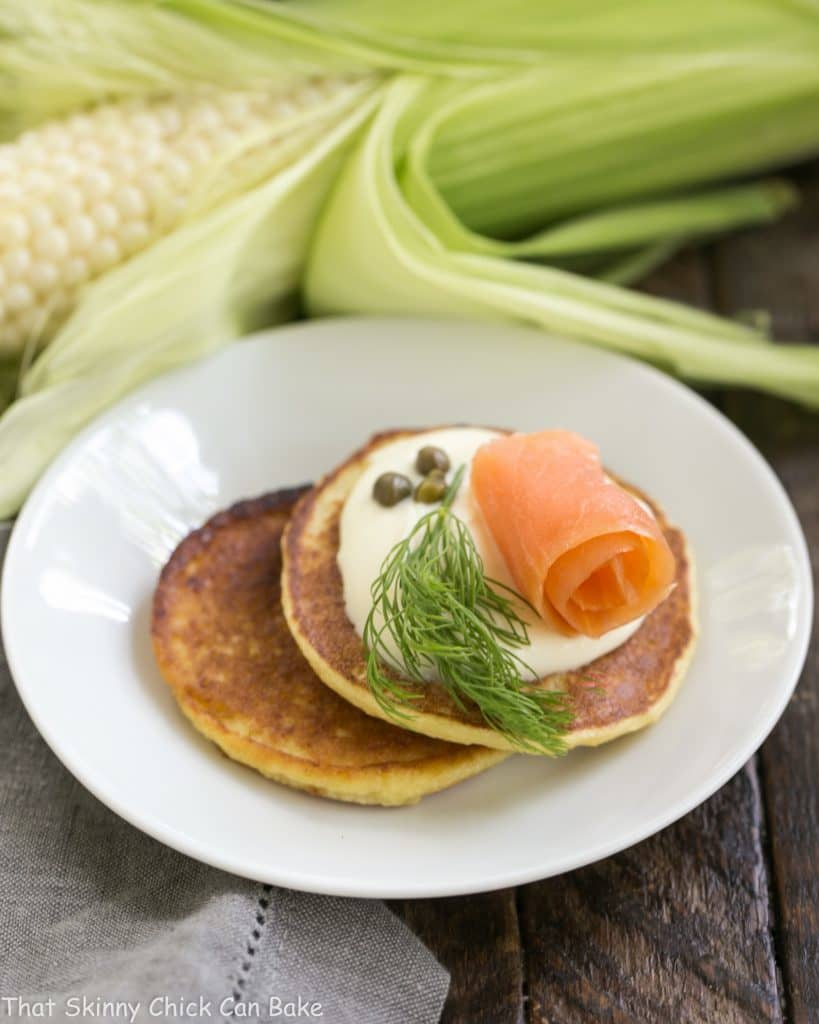 Savory Corn Cakes on a round white plate with toppings