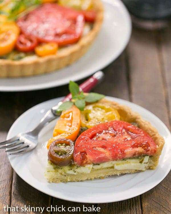 Slice of Fresh Tomato Tart on a small white plate with a red handled fork