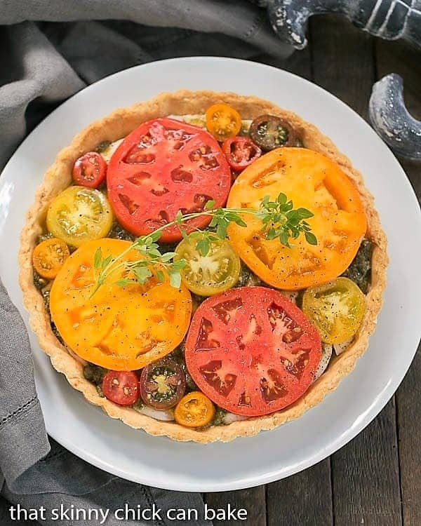 Overhead view of aFresh Tomato Tart on a serving plate garnished with herbs