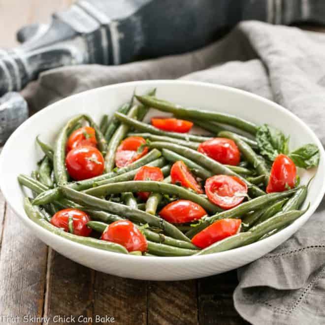 Haricot Verts with Grape Tomatoes in a white ceramic bowl with a garnish of fresh basil