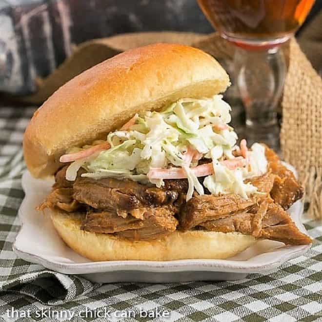 Pulled Pork Sandwiches topped with slaw on a white plate