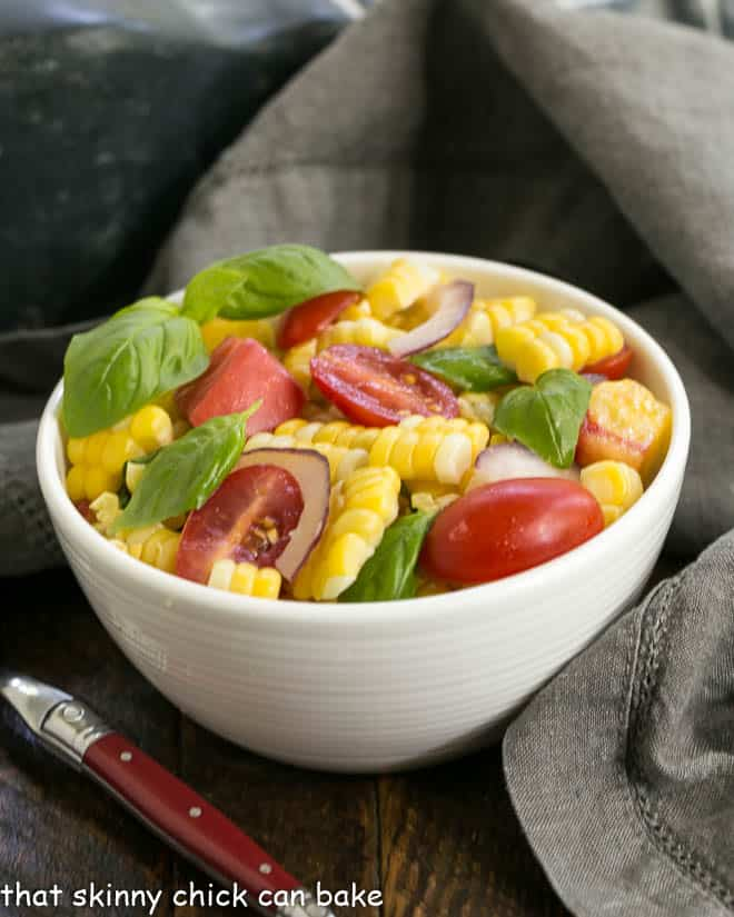 Small bowl of fresh corn basil and tomato salad with a red handle fork