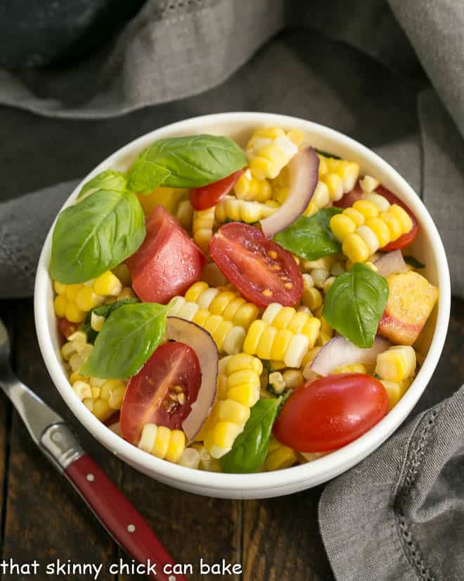 Small white bowl filled with corn, tomato and basil salad