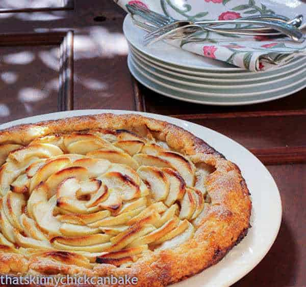 Apple Crostata on a white plate with dessert plates and forks in the background