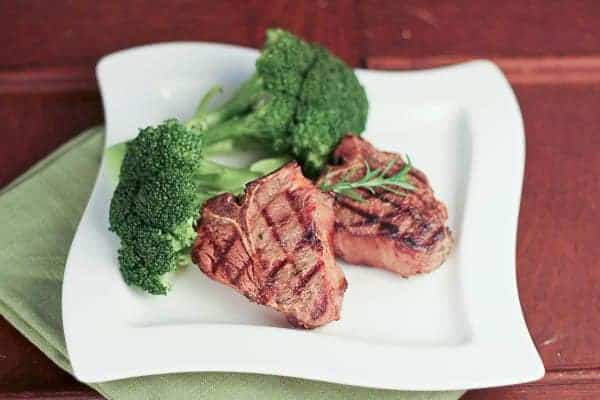 Marinated Lamb Chops on a white plate with broccoli