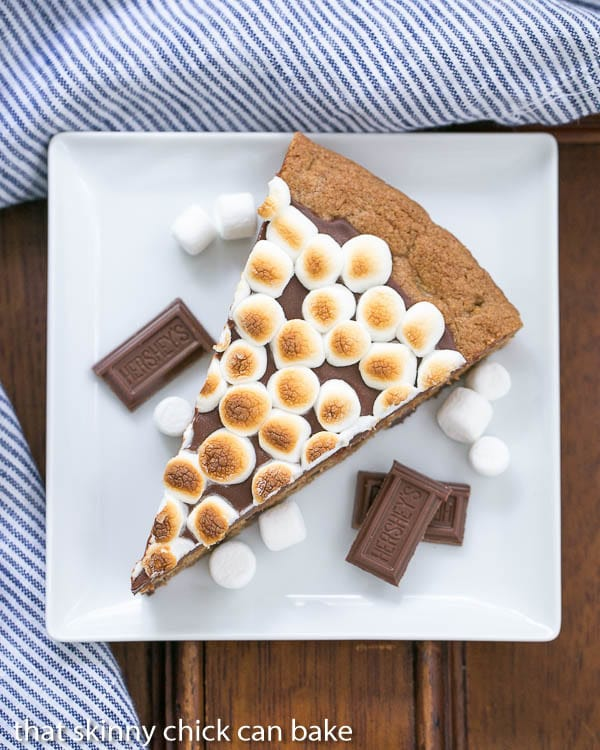 S'mores Cookie Cake wedge on a square white plate with chocolate bar squares and mini marshmallow garnishes