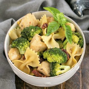 Overhead view of Chicken with Broccoli, Sun-dried Tomatoes and Bow Tie Pasta in a white ceramic bowl