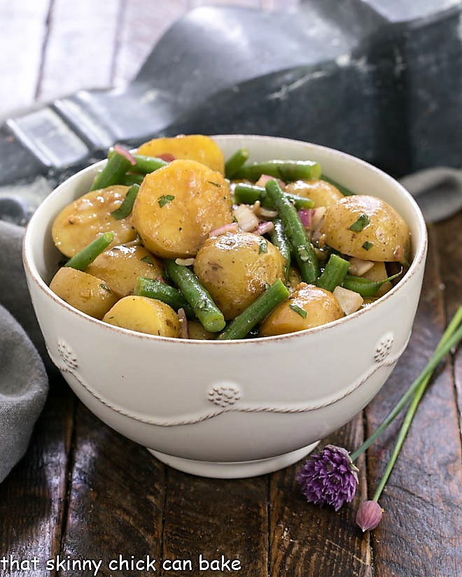 Homemade potato salad with green beans in a white serving bowl