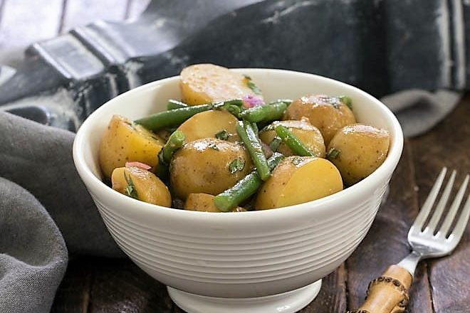 Homemade potato salad with green beans in a white bowl