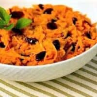 Grated Carrot Salad in a white serving bowl speckled with dried cranberries