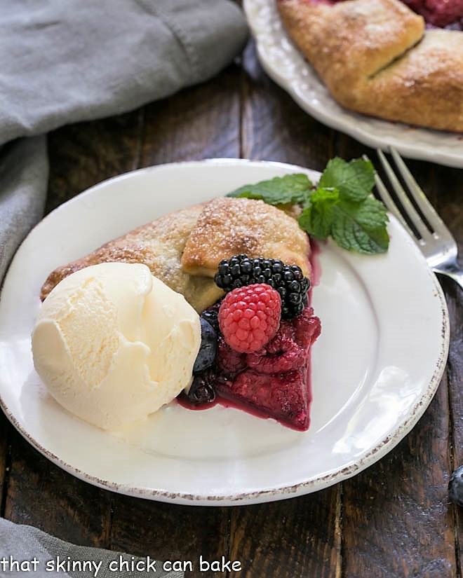 Slice of berry galete on a round white plate with a scoop of vanilla ice cream