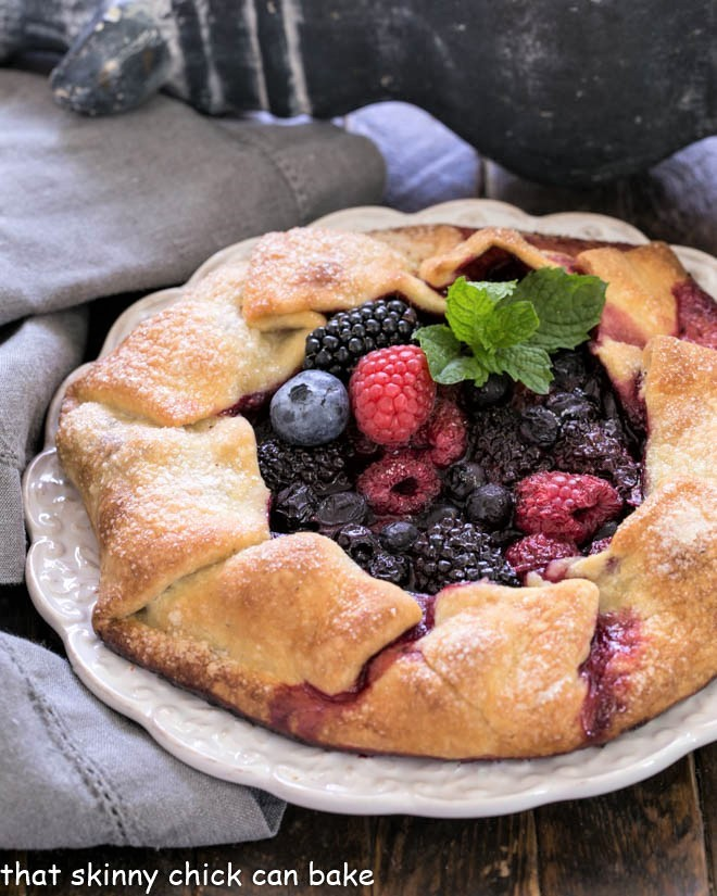 Mixed berry galette with a sprig of mint on a decorative white serving plate