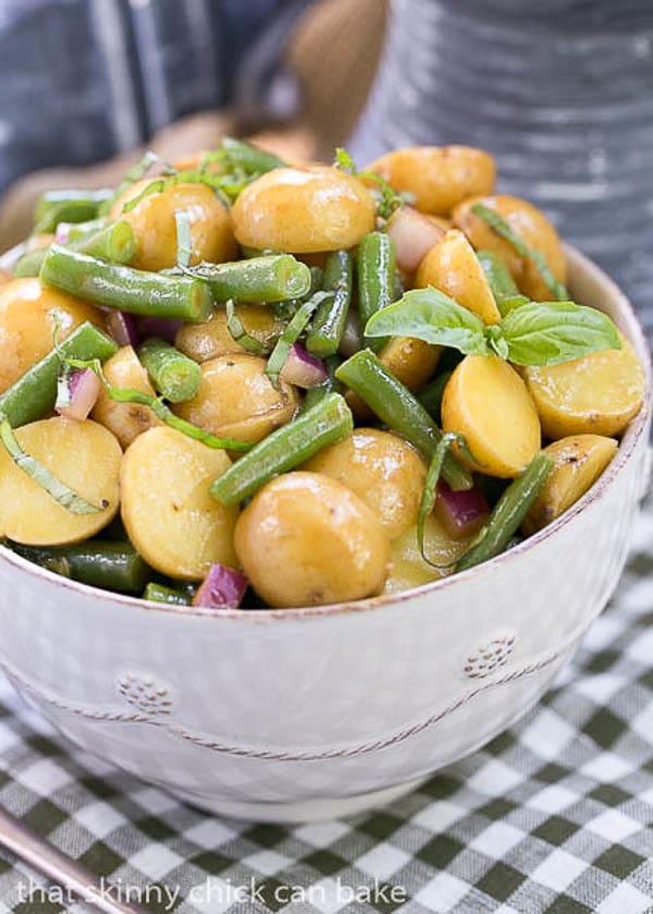 Potato and Green Bean Salad with Dijon Vinaigrette in a white bowl on a green and white checked napkin