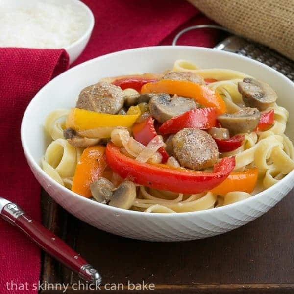 Sausage, Pepper, Mushroom Fettuccine in a white bowl with a red handle fork