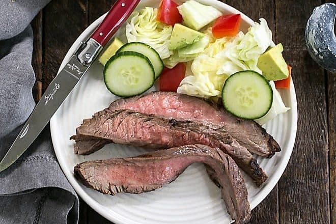 Overhead view of marinated flank steak slices on a white plate with a side of tossed salad