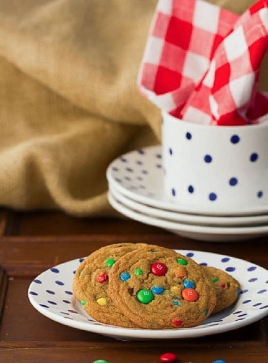 Brown Butter M&M Cookies on a serving late with more plates in the background