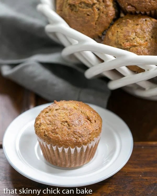 Buttermilk Bran Muffins in a white basket with a single muffin in the foreground