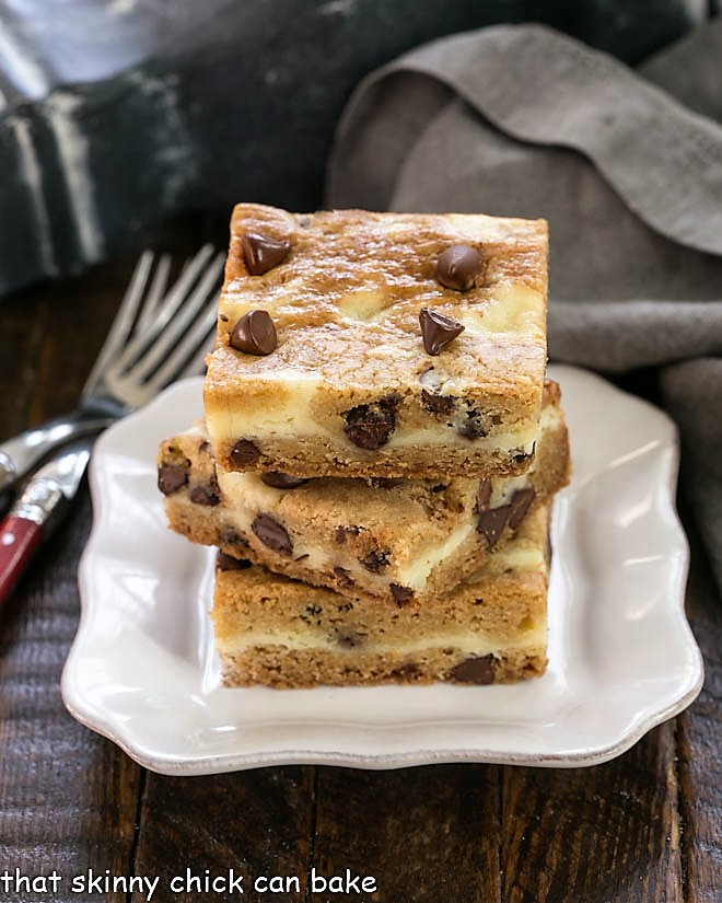 3 Cheesecake Filled Chocolate Chip Bars stacked on a square white plate