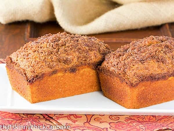 Two loaves of Streusel Topped Pumpkin Bread on a white platter