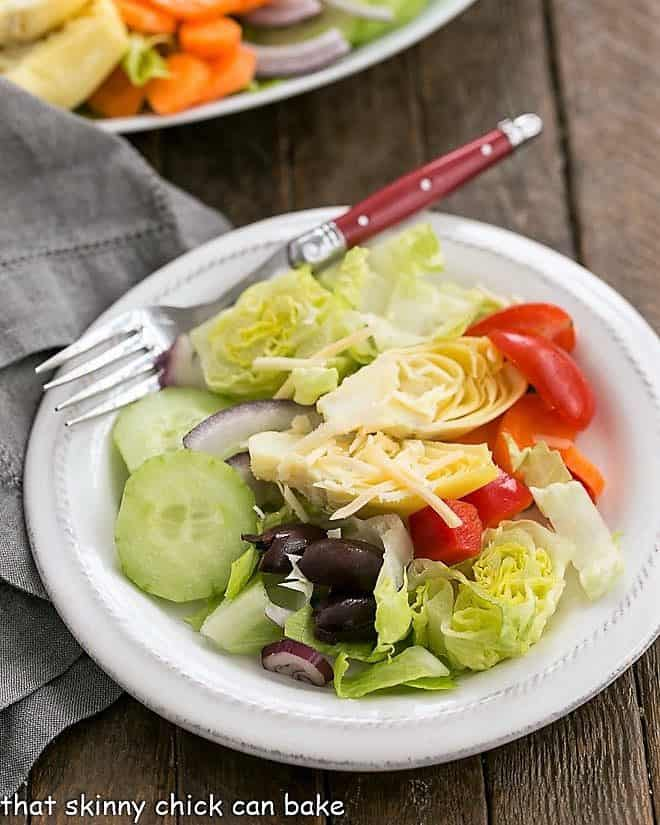 Kitchen Sink Chopped Salad on a white salad plate with a red handled fork