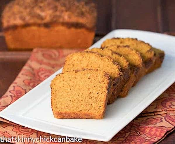 Streusel Topped Pumpkin Bread sliced on a white ceramic tray