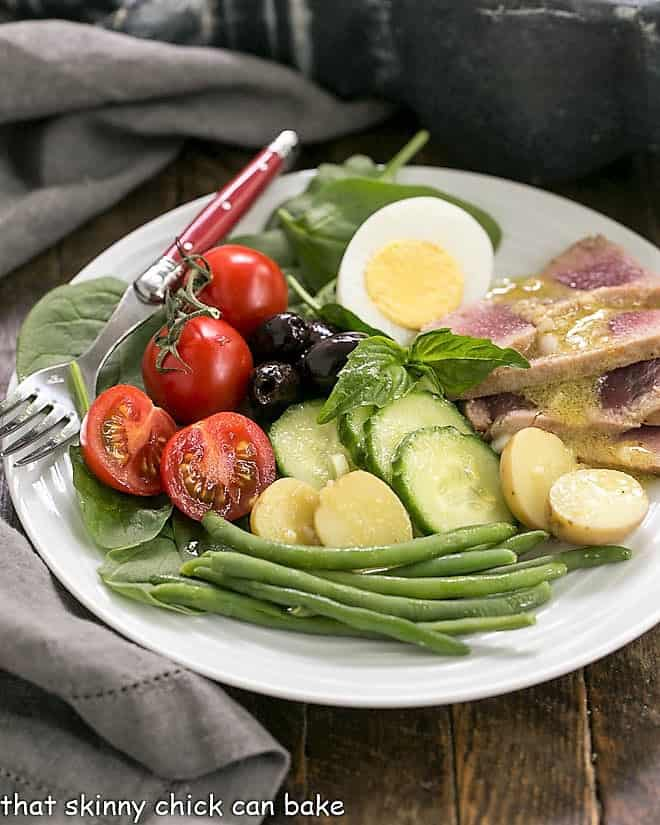 Ahi Tuna Salade Niçoise on a white salad plate with a red handled fork
