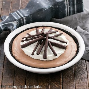 Chocolate pie in a white pie plate topped with whipped cream and chocolate curls