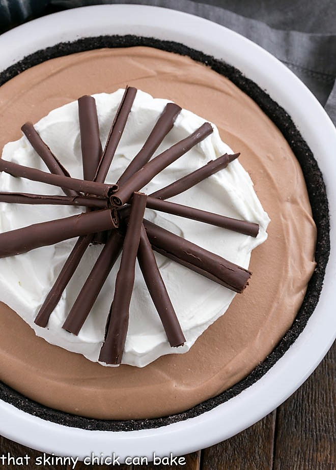Overhead view of Candy Bar Pie garnished with chocolate and whipped cream in a white pie plate.