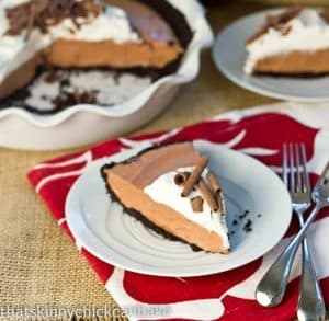 Slice of Candy Bar Pie on a small white serving plate with two silver forks.