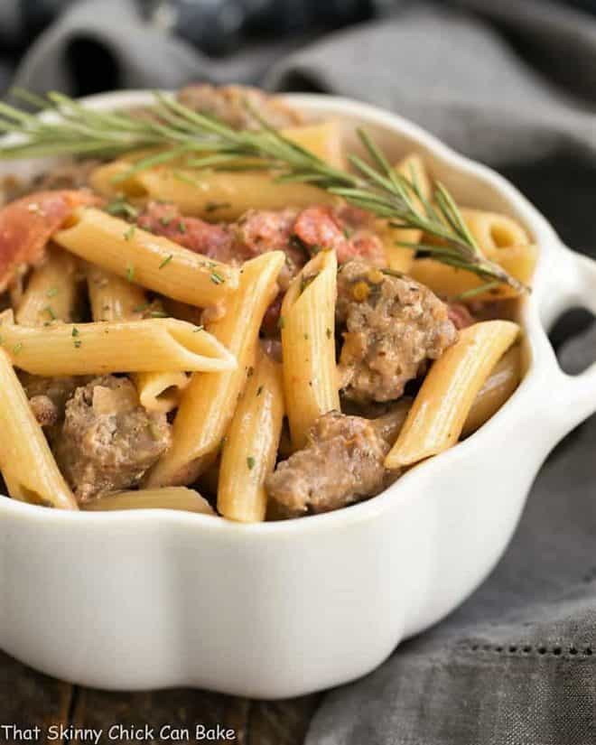 Creamy Italian Sausage Pasta in a white casserole dish garnished with rosemary