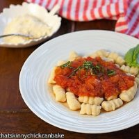Ricotta Gnocchi topped with marinara and fresh basil on a white dinner plate