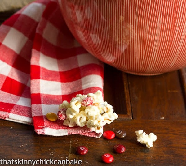 Holiday White Chocolate Popcorn in front of a serving bowl with M&M's