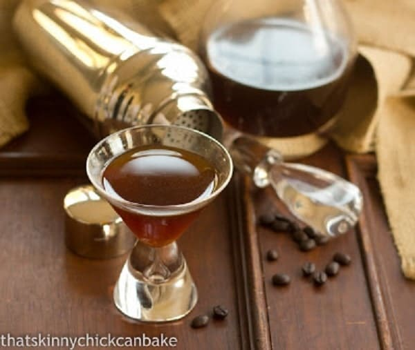 Homemade Kahlua in a glass with a decanter and coffee beans