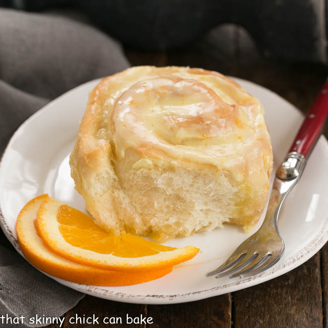 Orange Roll on a round white plate with two orange slices and a red handled fork