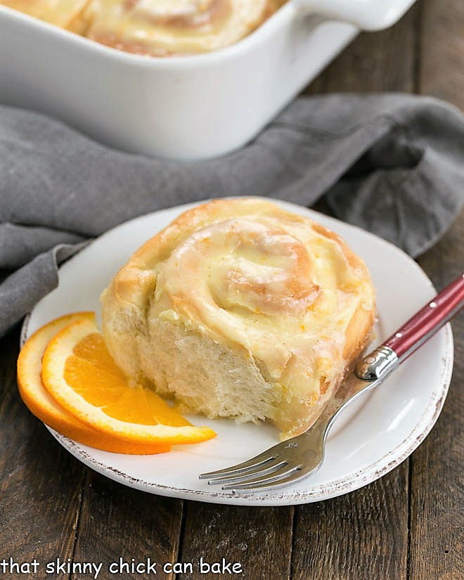 Orange Sweet Rolls in a baking dish with one roll in front on a small plate with a red handled fork
