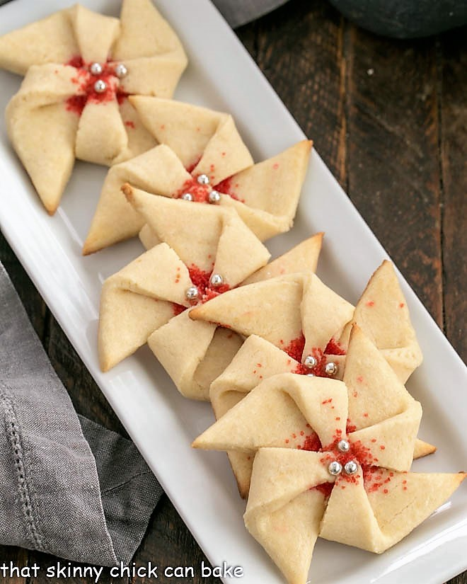 Overhead view of festive pinwheel cookies on a white tray