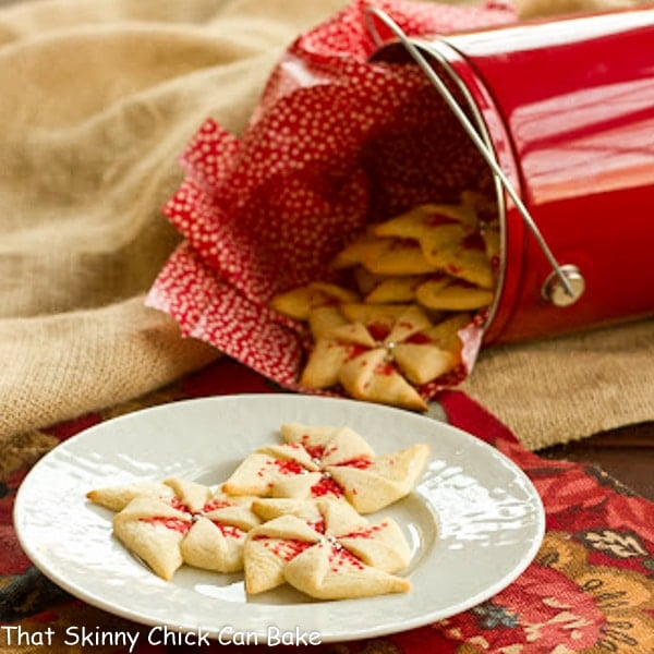 Large white plate of Poinsettia Cookies with a red bucket in the background full of Poinsettia Cookies.